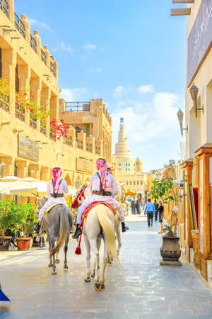 Doha, Qatar - February 20, 2019: Heritage Police Officers in traditional Qatari uniform at old Souq Waqif riding Arabian Horses. Fanar Islamic Cultural Center with Spiral Mosque on background Vertical