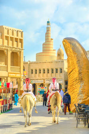 Doha, Qatar - February 20, 2019: police officers riding white Arabian horses at Souq Waqif market. Fanar Islamic Cultural Center with Spiral Mosque and golden thumb sculpture on background. Vertical. Editorial