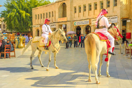 Doha, Qatar - February 20, 2019: Police on horse in traditional clothes at old Souq Waqif riding white Arabian Horses on pedestrian road. Popular tourist attraction in Middle East, Arabian Peninsula.