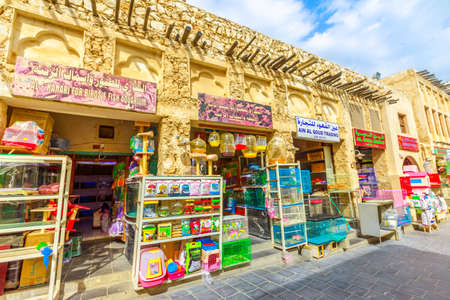 Doha, Qatar - February 19, 2019: pet shop and cages along pedestrian road inside Bird Souq near Souq Waqif, the old market and popular tourist attraction in Doha center, Middle East, Arabian Peninsula