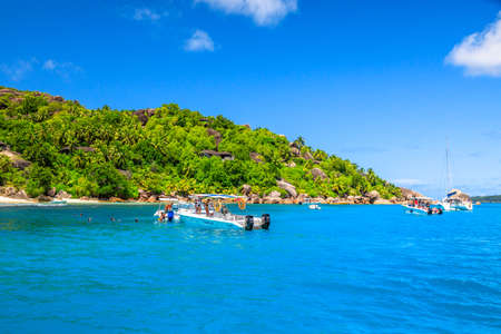 Felicite Island, Seychelles - May 3, 2019: sailboats, catamarans and snorkelers at Felicite Island Marine Park. Granite boulder stones and turquoise bay landscape. Tropical snorleling destination. Editorial