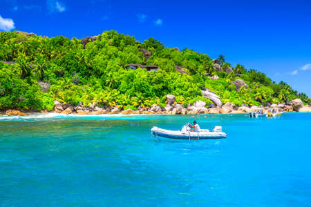 Felicite Island, Seychelles - May 3, 2019: sailboat, motorboat and snorkelers at Felicite Island Marine Park. Granite boulder stone and turquoise clear sea landscape. Tropical snorleling destination.