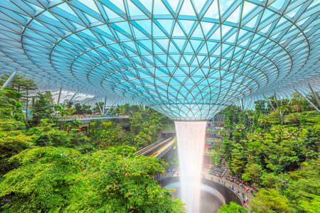 Singapore - Aug 8, 2019: aerial view of Rain Vortex, the worlds largest indoor waterfall surrounded by a four-story terraced forest and skytrain in Jewel Changi Airport opened on April 2019. Editorial