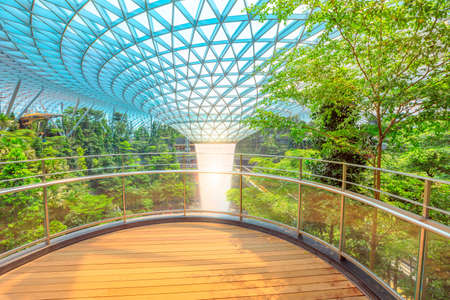 Singapore - Aug 8, 2019: scenic Rain Vortex, the worlds largest indoor waterfall surrounded by a four-story terraced forest in Jewel Changi Airport opened on April 2019.