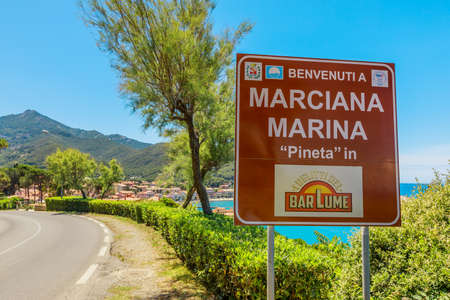 Marciana Marina, Elba island, Italy - June 17, 2020: Welcome sign Marciana Marina tourist resort famous for TV series The crimes of BarLume taken from a bestseller. Scenic panoramic landscape.