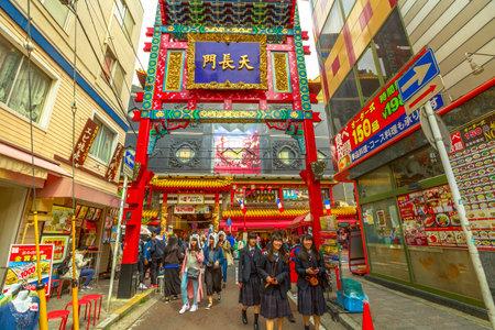 Yokohama, Japan - April 21, 2017: people and asian girls in school uniform walking near the gate in Yokohama Chinatown, the Japans largest Chinatown. Urban pedestrian street area. Editorial