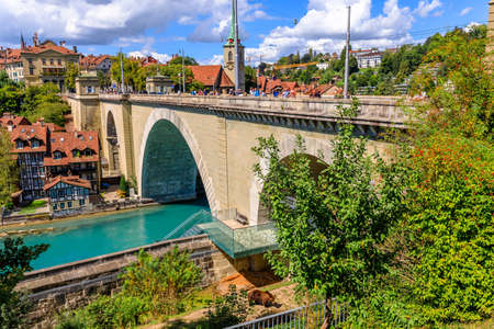 Bern, Switzerland - Aug 23, 2020: tourists looking a bear swimming in inside the Bear Pit from Nydeggbrucke bridge. tourist destinations in Bern, Switzerland. The Bear Park overlooks Aare River.