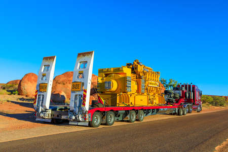 Northern Territory, Australia - August 12, 2019: red Kenworth truck of Clein Group crossing the Karlu Karlu, Devils Marbles Conservation Reserve in Northern Territory of Australian Outback at sunset.