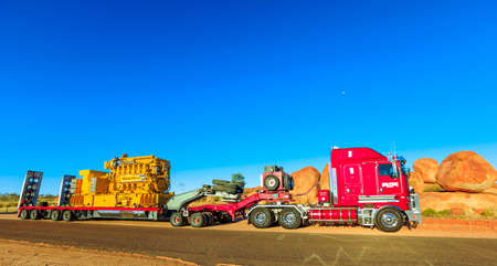 Northern Territory, Australia - August 12, 2019: red Kenworth truck of Clein Group crossing the Karlu Karlu, Devils Marbles Conservation Reserve in Northern Territory of Australian Outback.