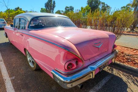 Yulara, Northern Territory, Australia - Aug 24, 2019: rear view of luxurious vintage pink Chevrolet Bel Air III car, close to Uluru-Kata Tjuta National Park. Famous classic car made in 1958 in America