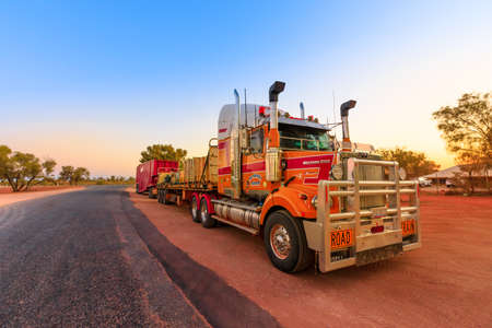 Ghan, Northern Territory, Australia - August 2019: Western Star road-train truck of Western Star road-train truck of Neil Mansell transport service. Crossing A87 Stuart highway of Australian Outback.