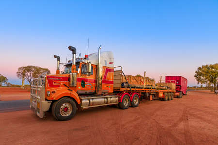 Ghan, Northern Territory, Australia - August 2019: Western Star road-train truck of Western Star road-train truck of Neil Mansell transport service. Crossing A87 Stuart highway of Outback at sunset Editorial