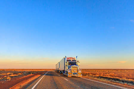 Northern Territory, Australia - August 29, 2019: Gilberts road-train truck of Kenworth crossing the highways of the Northern Territory of Australian Outback at sunset. Editorial
