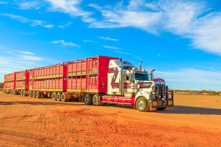 Marla, South Australia, Australia - August 29, 2019: Kenworth road-train truck of Hayson Haulage of Alice Springs. Crossing Marla town on A87 Stuart highway of Australian Outback. Editorial