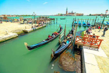 Venice, Italy - May 9, 2021: Traditional gondola boats with tourists in tour on Canal of Giudecca by Saint Mark square. San Giorgio island on background. People with mask for Coronavirus Covid19.