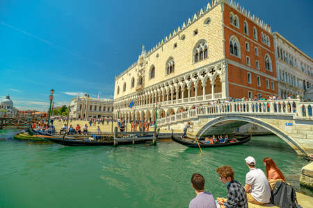 Venice, Italy - May 9, 2021: traditional gondolas for touristic cruise on Giudecca Canal by Saint Mark square with Doges palace. The main and biggest canal of Venice.