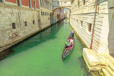 Venice, Italy - May 9, 2021: romantic gondola touristic cruise under the Sospiri arcade bridge leading to old prisons of Doge Palace. Narrow canals of Venice through Venetian water roads.