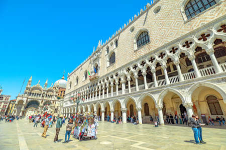 Venice, Italy - May 9, 2021: People with surgical mask for Coronavirus Covid-19 pandemic in the Saint Mark square of Venice. With Doges palace of Venice Italian city.