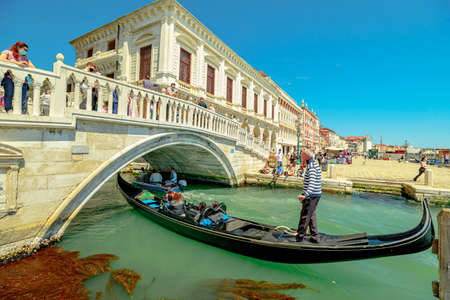 Venice, Italy - May 9, 2021: Saint Mark square and traditional gondola boats with tourists in tour on Canal of Giudecca. People with face mask for Covid-19 Coronavirus pandemic. Editöryel