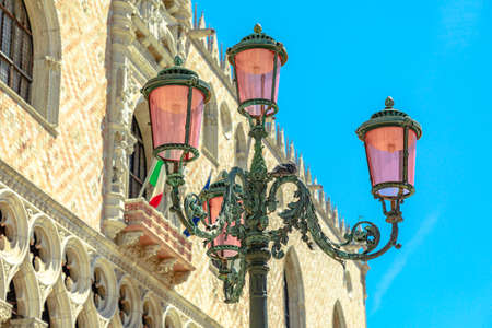 Details of Venetian famous street lamps of the San Marco square in Venice city downtown. Saint Mark Italian square of Venice city of Italy with Doges palace colonnade behind.