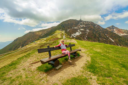 Sporty woman in a trekking dress on top of Tamaro mount in Switzerland. Swiss bench by the pond in Foppa alp in Ticino canton. Top of Rivera station of cable car. Stok Fotoğraf