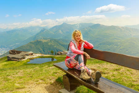 Backpacker girl in a trekking dress enjoying Tamaro mount in Switzerland. Swiss bench by the pond in Foppa alp in Ticino canton. Top of Rivera station of cable car. Stok Fotoğraf