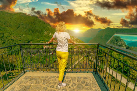 elegant woman at sunset on top of Lugano Swiss city by Lugano Lake in Switzerland. Aerial view lookout from Monte Bre Mount. Lugano cityscape with Bre Village in Ticino canton.