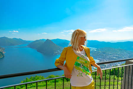 elegant woman on top of Lugano Swiss city by Lugano Lake in Switzerland. Aerial view lookout from Monte Bre Mount. Lugano cityscape with San Salvatore mount in Ticino canton.