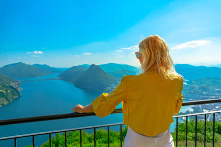backside of a woman on top of Lugano Swiss city by Lugano Lake in Switzerland. Aerial view lookout from Monte Bre Mount. Lugano cityscape with San Salvatore mount in Ticino canton. Stok Fotoğraf