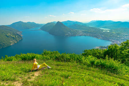 Swiss elegant woman sitting on top of Lugano corniche by Lugano Lake in Switzerland. Aerial view lookout from Bre Mount. Lugano cityscape with San Salvatore mount in Ticino canton.