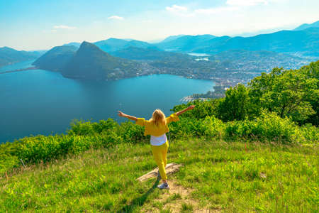 Swiss elegant woman with open arms on top of Lugano corniche by Lugano Lake in Switzerland. Aerial view lookout from Bre Mount. Lugano cityscape with San Salvatore mount in Ticino canton. Stok Fotoğraf