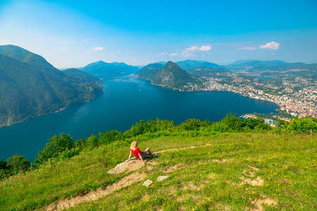 Woman sitting on top of Lugano Swiss city by Lugano Lake in Switzerland. Aerial view lookout from Monte Bre Mount. Lugano cityscape with San Salvatore mount in Ticino canton.