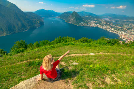 Girl showing Lugano Swiss city by Lugano Lake in Switzerland. Aerial view lookout from Monte Bre Mount. Lugano cityscape with San Salvatore mount in Ticino canton. Stok Fotoğraf
