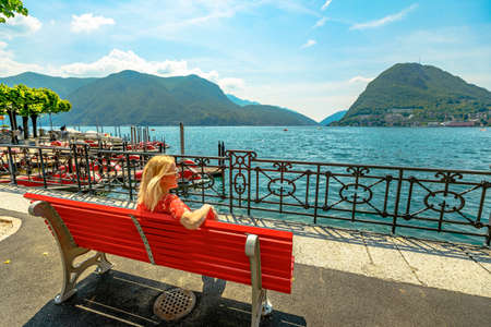 Elegant woman in a red dress enjoying Lugano city on Lugano Lake in Switzerland. Red bench by the lakefront of Lugano Lake with Monte San Salvatore mount in Ticino canton. Stok Fotoğraf