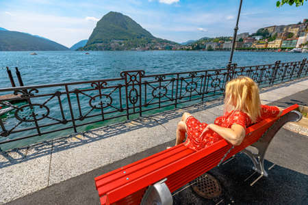 Elegant girl in a red dress enjoying Lugano city on Lugano Lake in Switzerland. Red bench by the lakefront of Lugano Lake with Monte San Salvatore mount in Ticino canton.