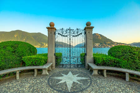 Gate on the Lugano Lake in the public Ciani park of Switzerland. The lakefront of Lugano city in Ticino canton. Park bench with wind rose of stones and with Monte San Salvatore mount. Stok Fotoğraf