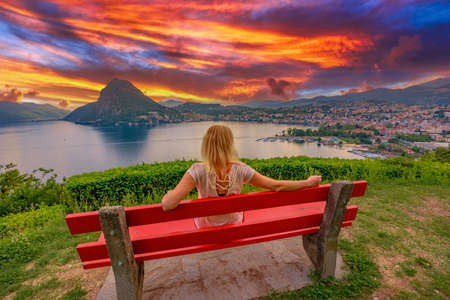 Tourist girl on top of Lugano city at sunset by Lugano Lake in Switzerland. Red bench at lookout with aerial view from San Michele hill. Lugano cityscape with San Salvatore mount in Ticino canton.