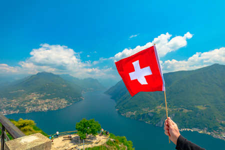 Hand with Swiss flag on top of Lugano skyline from San Salvatore peak in Ticino canton. Lugano Lake in Switzerland. Aerial view lookout from San Salvatore Mount. Stok Fotoğraf