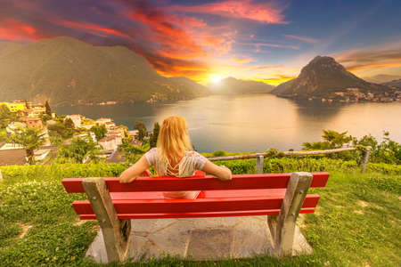 Woman on top of Lugano city by Lugano Lake in Switzerland. Red bench at lookout with aerial view from San Michele hill. Lugano cityscape with San Salvatore mount in Ticino canton.