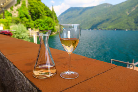rose wine by the lakefront of Lugano city in Switzerland. Romantic appetizer in Ticino Canton on Swiss Lake Lugano. Olive trees pathway of Lugano in Switzerland. Stok Fotoğraf