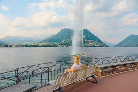 woman looking the water jet of Paradiso fountain of Lugano city in Lugano Lake of Switzerland. Sitting on the bench by the waterfront of Lugano Lake with Monte San Salvatore mount in Ticino canton.