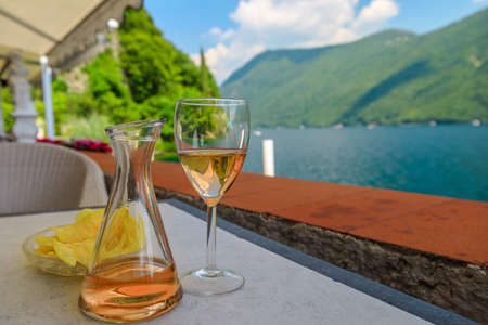 rose wine flute by the lakefront of Lugano city in Switzerland. Romantic appetizer in Ticino Canton on Swiss Lake Lugano of Switzerland. Olive trees pathway of Lugano.
