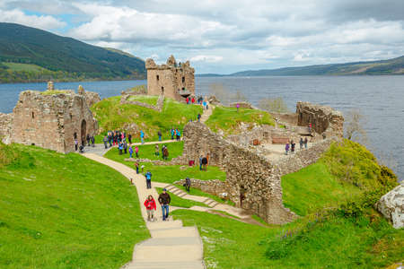 Loch Ness, Scotland, United Kingdom - May 24, 2015: top view of tourists visiting Urquhart Castle beside Loch Ness lake. Visited for the legend of the Loch Ness monster: Nessie. Editöryel