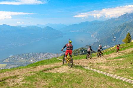 Verzasca, Switzerland - June 2021: bikers by mountain bike descending down from top of Cardada-Cimetta mount in Switzerland. Swiss chairlift skyline of Locarno and Ascona on Lake Maggiore in Ticino.