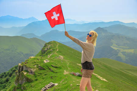 Tourist woman with swiss flag on Monte Generoso Calvagione top. Skyline view of Lugano lake of Ticino canton. Top of cog train station in Mendrisio district, Switzerland.