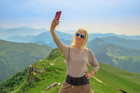 Tourist woman taking selfie pictures on Monte Generoso skyline or Calvagione Swiss mount of Ticino canton. Top of the cog train station in Mendrisio district, Switzerland.