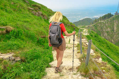 Tourist woman backpacker trekking in Monte Generoso or Calvagione Swiss mount. Skyline of Lugano lake of Ticino canton. Top of cog train station in Mendrisio district, Switzerland.