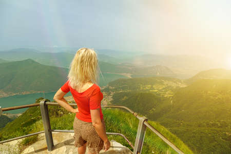 Tourist woman at sunset on top view of Monte Generoso or Calvagione Swiss mount. Aerial skyline of Lugano lake of Ticino canton. Top of cog train station in Mendrisio district, Switzerland.