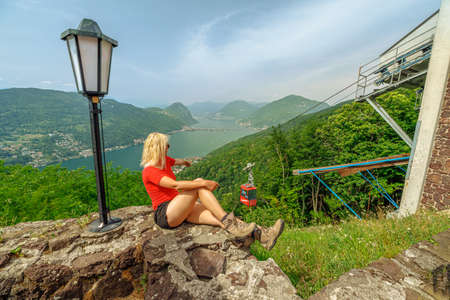 Woman relaxing on top of San Giorgio mount in Brusino Alps of Switzerland. Swiss cable car Brusino-Serpiano. Brusino Arsizio town cityscape in Ticino canton with Lugano lake. Stok Fotoğraf