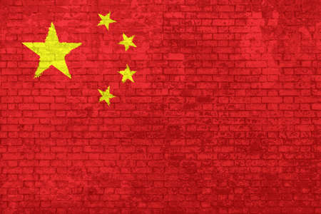wall of bricks painted with the Chinese flag with five yellow stars on red background. Concept of social barriers of immigration, divisions, and political conflicts in China. Stok Fotoğraf